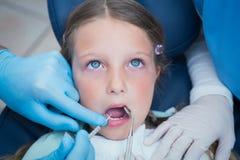 Zahnarzt mit Assistenzden untersuchungsmädchenzähnen Lizenzfreie Stockfotografie