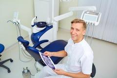 Zahnarzt mit Bild in den Händen des Arbeitsplatzkrankenhauses sein Büro Stockbild