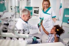 Zahnarzt mit seinem Patienten, der fünf im zahnmedizinischen Krankenwagen gibt Lizenzfreie Stockbilder