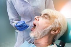 Zahnarzt mit Untersuchungspatienten des Spiegels stockfotografie