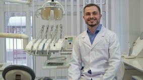 Zahnarzt setzt sich auf dem Stuhl in seinem Büro hin stock video footage