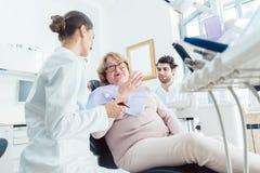 Zahnarzt und Assistent, die älteren Patienten grüßen Stockbild