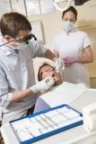 Zahnarzt und Assistent im Prüfungraum mit Mann stockbild