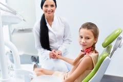 Zahnarzt und Patient im Zahnarztbüro Kind im zahnmedizinischen Stuhl Lizenzfreie Stockbilder