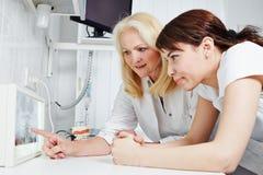 Zahnarzt und zahnmedizinisches assistand, die Röntgenstrahlbild betrachten Stockfoto