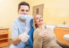 Zahnarztdoktor und -patient, die sich Daumen zeigen Lizenzfreie Stockfotografie