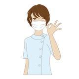 Zahnarzthelfer, der mit OKAYzeichen aufwirft Stockbild