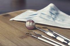 Zahnarztwerkzeuge und -maske mit Reflexion von Zähnen Lizenzfreie Stockfotos
