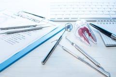 Zahnarztwerkzeuge, Zahndurchbruchdiagramm und Zahn modellieren auf Tabelle mit Computertastatur und zahnmedizinische Sonde des No stockfoto