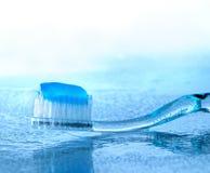 Zahnbürste mit Paste auf nassem Glas lizenzfreie stockfotografie