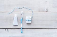 Zahnbürste, Zahnpasta und Zahnseide auf einer verwitterten Holzrückseite stockfotografie