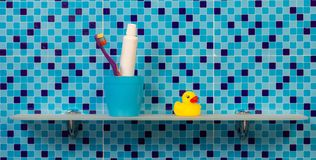 Zahnbürsten im Glas auf Badezimmerregal Lizenzfreie Stockfotos