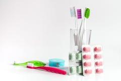 Zahnbürsten im Glas auf weißen Hintergrundwerkzeugen für Zahnpflege Lizenzfreie Stockfotos