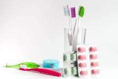 Zahnbürsten im Glas auf weißen Hintergrundwerkzeugen für Zahnpflege Lizenzfreies Stockfoto