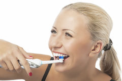 Zahngesundheit: Kaukasische blonde Frau, die ihre Zähne durch die Anwendung putzt Lizenzfreie Stockfotos