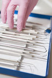 Zahnmedizinische Hilfsmittel mit einer behandschuhten Hand Lizenzfreie Stockfotos