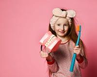 Zahnmedizinische Hygiene glückliches kleines nettes Mädchen mit Zahnbürsten stockfotografie