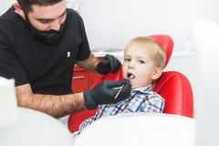 Zahnmedizinische Klinik Aufnahme, Pr?fung des Patienten Zahnsorgfalt Zahnarzt, der Z?hne des kleinen Jungen im Zahnarztb?ro behan stockfoto