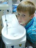 Am zahnmedizinischen geduldigen Spuckenwasser des Zahnarztes Stockfotografie