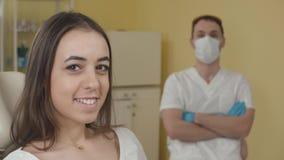 Zahnmedizinisches Büro Glücklicher weiblicher Patient, der die Kamera betrachtet im Hintergrund ein Zahnarzt The-Konzept der Werb stock video