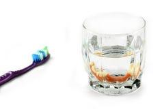 Zahnmedizinisches Gesundheitskonzept: teilweises Gebiss innerhalb des Glases nahe bei Zahnbürste lizenzfreies stockbild