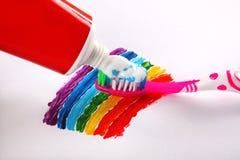 Zahnpasta und Zahnbürste auf Regenbogenhintergrund Stockfotos