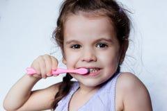 Zahnpflege - Reinigungszähne des kleinen Mädchens durch Zahnbürste lizenzfreie stockfotos