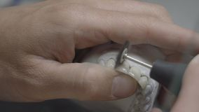 Zahntechniker, der k?nstliche Kieferform mit den Z?hnen h?lt und sie im Labor poliert B?rstende Z?hne des Zahnarztes mit Berufsw stock video footage