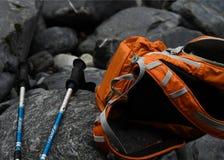 Zaino arancio e bastoni da passeggio blu sulle rocce immagini stock