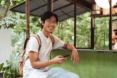 Zaino d'uso sorridente dell'uomo asiatico dello studente fotografia stock