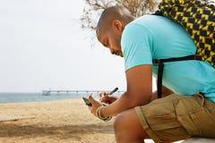 Zaino dell'uomo afroamericano pensieroso dei pantaloni a vita bassa e note d'uso di fabbricazione in quaderno fuori della città a Fotografia Stock Libera da Diritti