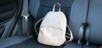 Zaino di cuoio beige su un sedile posteriore grigio di un'automobile immagine stock libera da diritti