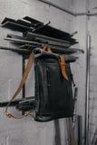 Zaino di cuoio nero esclusivo Zaino vicino alla parete Gli strumenti nel garage Tubi del metallo vicino alla parete Fotografia Stock