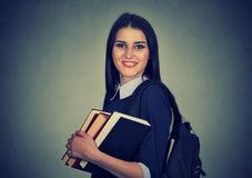 Zaino di trasporto sorridente e tenuta dello studente della pila di libri Fotografie Stock