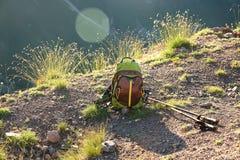 Zaino di trekking e pali di escursione sulla strada della montagna immagini stock libere da diritti