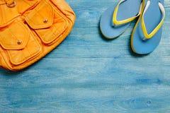 Zaino e pantofole gialli su una tavola di legno blu, vista superiore Immagine Stock