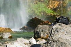 Zaino turistico sulla roccia della montagna, cascata serica su fondo immagine stock