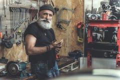 Zainteresowany brodaty dorośleć mężczyzna w warsztacie fotografia stock