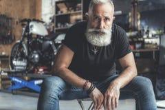 Zainteresowany stary człowiek w garażu zdjęcia stock