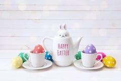 Zając z z wiadomości Szczęśliwą wielkanocą, filiżankami i jajkami na w, Obrazy Stock