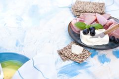 Zakąska ser i baleron na błękitnym tle talerza i światła Bezpłatna przestrzeń dla teksta lub reklamy obraz royalty free