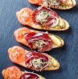 Zakąski bruschetta z prosciutto, pomidor, zucchini na ciabatta chlebie na kamienia łupku tła zakończeniu up zdjęcia stock
