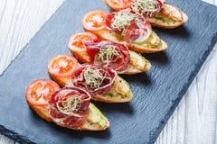 Zakąski bruschetta z prosciutto, pomidor, zucchini na ciabatta chlebie na kamienia łupku tła zakończeniu up Obrazy Stock