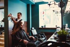 Zakład fryzjerski z drewnianym wnętrzem Brodaty wzorcowy mężczyzna i fryzjer męski zdjęcie royalty free