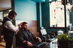 Zakład fryzjerski z drewnianym wnętrzem Brodaty wzorcowy mężczyzna i fryzjer męski obraz stock