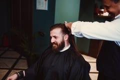 Zakład fryzjerski z drewnianym wnętrzem Brodaty wzorcowy mężczyzna i fryzjer męski zdjęcie stock