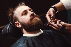 Zakład fryzjerski z drewnianym wnętrzem Brodaty wzorcowy mężczyzna i fryzjer męski zdjęcia royalty free
