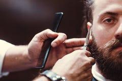 Zakład fryzjerski z drewnianym wnętrzem Brodaty wzorcowy mężczyzna i fryzjer męski obrazy stock