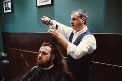 Zakład fryzjerski z drewnianym wnętrzem Brodaty wzorcowy mężczyzna i fryzjer męski obrazy royalty free