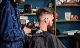 Zakładu fryzjerskiego pojęcie Modnisia brodaty klient dostać fryzurę Fryzjer męski z hairdryer dmucha z włosy z przylądka Fryzjer Zdjęcie Stock